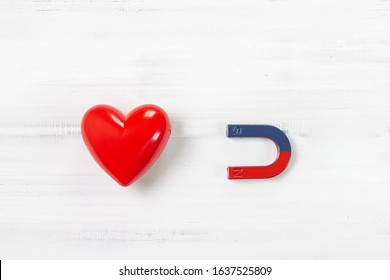 Magnet attracting Red Heart on white wood background. Love Concept with Copy Space.