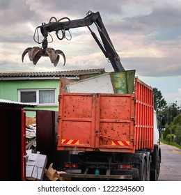 Magnet grapple picking up iron and steel metal garbage for transferring and recycling. Truck with metal grab is loading industrial and household waste on scrap yard. Demolition and sorting concept
