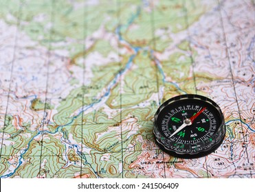 The magnetic compass is located on a topographic map. Satellites adventure - map and compass.