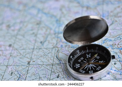 The magnetic compass is located on a topographic map. Equipment for travel - map and compass.