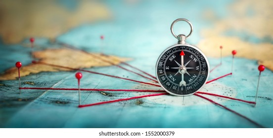 Magnetic compass  and location marking with a pin on routes on world map. Adventure, discovery, navigation, communication, logistics, geography, transport and travel theme concept background.