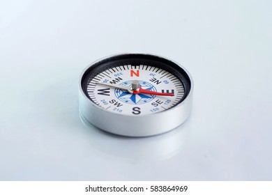 magnetic compass on isolated white background with mirror reflection