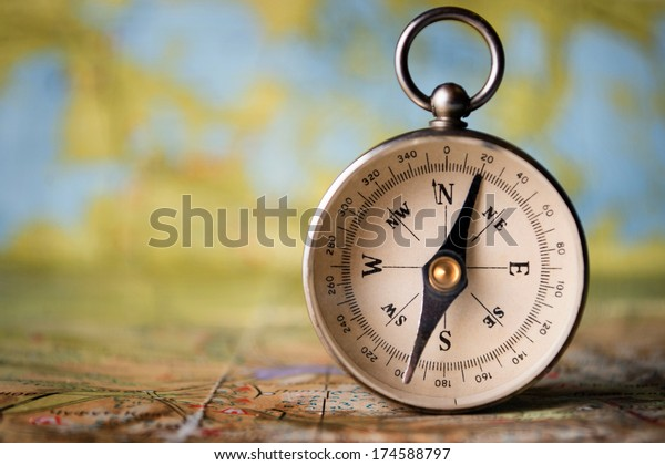 Magnetic compass standing upright on a world map conceptual of global travel , tourism and exploration, with copyspace
