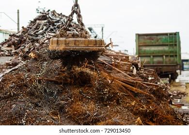 Magnetic crane loading scrap metals at junkyard