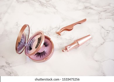 Magnetic fake artificial eyelashes in pink mirror kit, eye liner, tweezers isolated on marble background. Eyelash extension cosmetology tool concept, beauty treatment, improving physical appearance