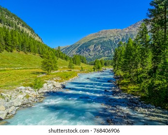 magnificant blue water coloured by the icewater of glaciers next to dark green forests and beautiful grasland in the swiss alps valley of val roseg near pontresina, st. moritz