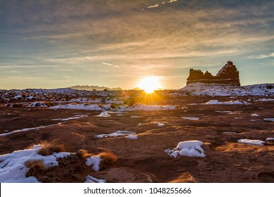 Magnificent Arches National Park at sunset in the winter with the sun glowing on the horizon in Moab, Utah USA.