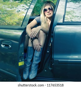 magnificent blonde driver girl with sunglasses sitting in blue colored car. outdoor shot