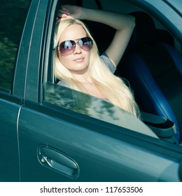 magnificent blonde girl with sunglasses sitting in blue colored car. outdoor shot