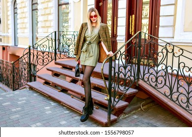 Magnificent blonde stylish woman posing on the straits near luxury classic style hotel, European atmosphere, modern trendy outfit, blogger posing on the street.