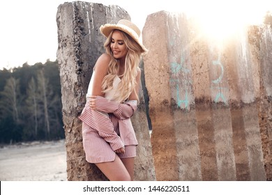 Magnificent, fashionable and romantic smiling young woman with long loose blonde hair in a straw hat enjoys her vacation. Countryside landscape, wild beach at the background. Summertime, summer