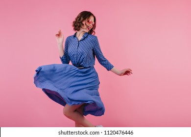 Magnificent female model in midi skirt dancing and laughing on pink background. Studio portrait of excited caucasian woman in blue clothes expressing positive emotions.