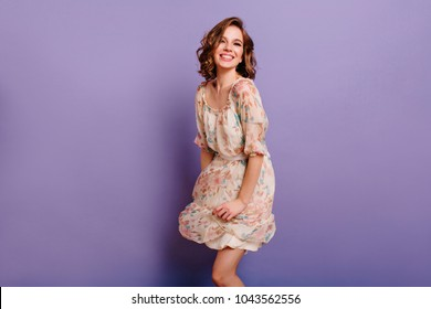Magnificent girl with light-brown curly hair dancing with smile in purple studio. Indoor portrait of inspired caucasian lady in romantic outfit expressing happy emotions.