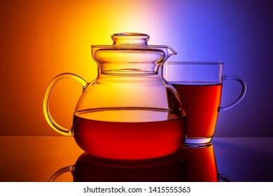 Magnificent glass teapot with a cup on a multi-colored background.
