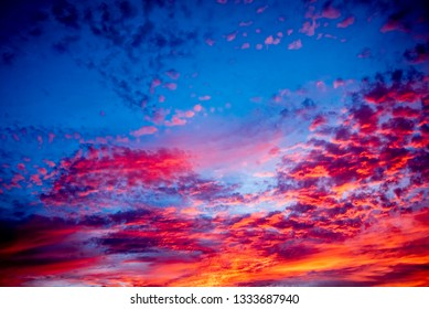 The magnificent interplay of beautiful colors of the deep blue sky and golden orange clouds after the setting of the sun.