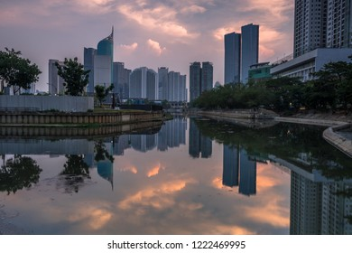 Magnificent of Jakarta cityscape. Office buildings reflected on the water with cloudy sky in the dusk, Jakarta, Indonesia