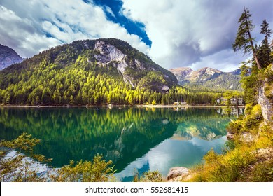 Magnificent lake Lago di Braies. South Tyrol, Italy. The concept of walking and eco-tourism. Emerald expanse of water reflects the surrounding forest and mountains