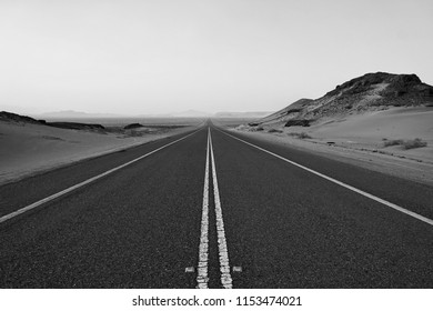 Magnificent perpective view of a road in the middle of dessert in black and white