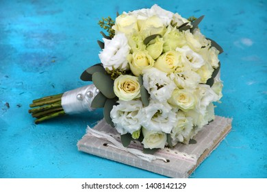 A magnificent round bridal bouquet lies on a book with a lace bow in vintage style on a turquoise background. Bouquet of Magadi Roses and White Lisianthus and Eustoma against the background of aqua