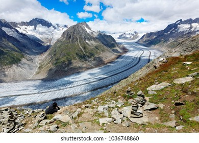 Magnificent scenery of Aletsch Glacier (Aletschgletscher) curving between rocky Alpine mountains & the shadows of clouds cast in the glacial valley in Eggishorn, Fiesch, Bernese Oberland, Switzerland