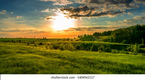 Magnificent scenery, sunset over fields, ravines and forests, turquoise orange sky and bright green grass and leaves of trees.