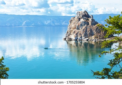 Magnificent summer landscape with Baikal Lake on a sunny day. Tourists travel in a rubber boat around the famous Shaman Rock. Flocks of June midges are visible on water. Natural background