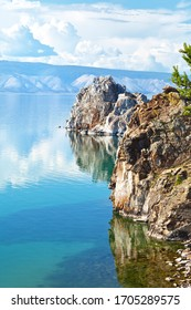 Magnificent summer landscape with Baikal Lake on a sunny day. Two famous rocks of Olkhon Island - Shamanka and Hero Rocks are reflected in calm water. Summer travel, natural background