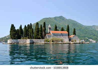 The magnificent sunny day in the most beautiful fjord in Europe, Boka Kotor bay in Montenegro - a small historical church on the island near Perast city and the tranquil surface of Adriatic sea