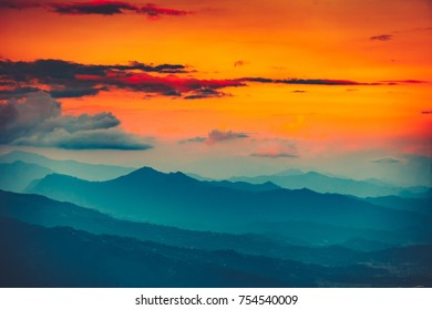 Magnificent sunset views of the mountain range with the altitude of the aircraft. Picturesque and gorgeous evening scene with bright orange sky. Color toning effect. Beauty world.