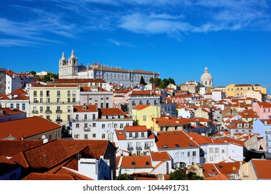 The magnificent view of Alfama district in Lisbon, Portugal, with traditional old yellow houses and red roofs.