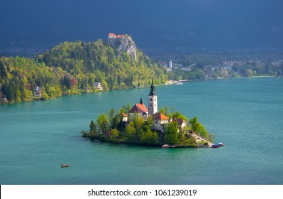 Magnificent view of Bled Lake. Azure water, Bled island with pilgrimage church of the Assumption of Mary and Bled castle on rock in sunlit, Slovenia