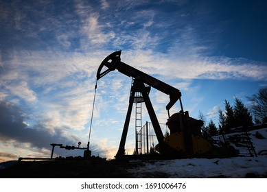 Magnificent view of evening cloudy sky over petroleum pump jack. Oil field with artificial lift pump system or oil pump rocker-machine. Concept of petroleum industry and oil extraction.