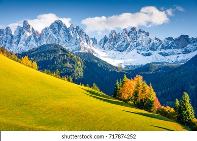 Magnificent view of Santa Magdalena village hills in front of the Geisler or Odle Dolomites Group. Colorful autumn scene of Dolomite Alps, Italy, Europe. Beauty of nature concept background.