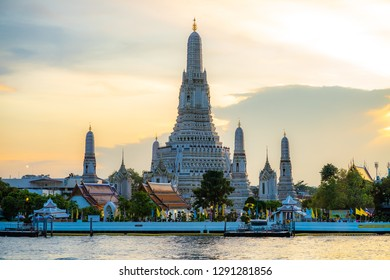 Magnificent view of the Temple of Dawn by the Chao Phraya river during sunset with beautiful shades of colors in the sky.