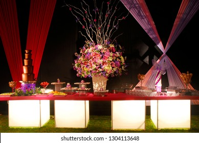 Magnificent wedding desserts table with chocolate fondue fountain, luxurious floral display and decorative fabrics in the background.