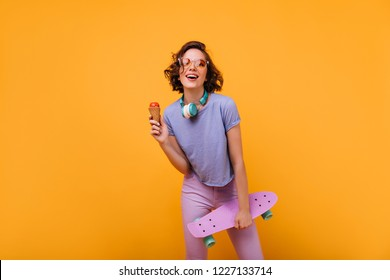 Magnificent white girl in casual clothes posing in headphones. Studio portrait of beautiful lady with skateboard eating ice cream on orange background.