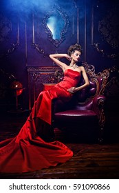 Magnificent young woman in luxurious red dress and precious jewelery is sitting in a chair in a luxury apartment. Classic vintage interior. Beauty, fashion.