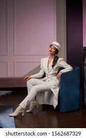 Magnificent young woman with red lips wearing stylish plaid longline blazer and cap sitting in modern armchair. Glamorous female model dressed in trendy white suit. Caucasian girl in classy jacket.
