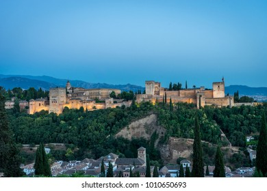 The magnificient Alhambra of Granada, Spain. Alhambra fortress at sunset viewed from Mirador de San Nicolas during evening twilight hour.