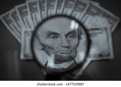 A magnified image of Abraham Lincoln with other bills in the background