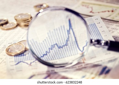 Magnifier focuses a chart with a rising curve.