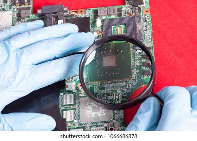 Magnifier in hands with blue  gloves showing or looks on printed circuit board, PCB