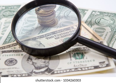 Magnifier lies on small bills of American dollars