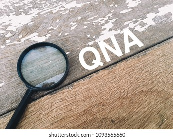 Magnifier over the wooden table written QNA