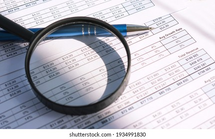 Magnifier and pen lies on a white documents background