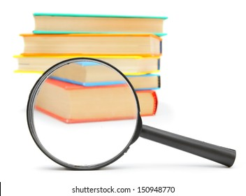 Magnifier and pile of multi-coloured books. On a white background.