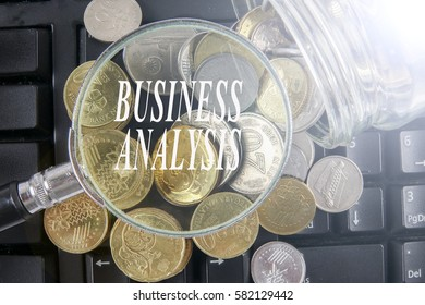 Magnify glass and coins on keyboard. Business analysis concept.