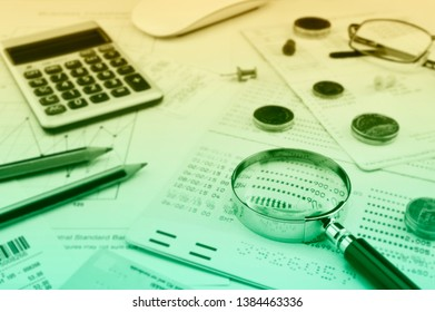 Magnifying glass, account book, pencil, coins, and calculator on paper graph, Business saving concept