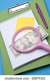 Magnifying glass analysis of business or education costs.