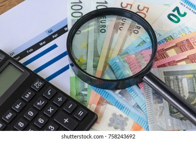 Magnifying glass and black calculator on pile of Euro banknotes with printed quarter chart graph as Euro economy or debt analysis concept.